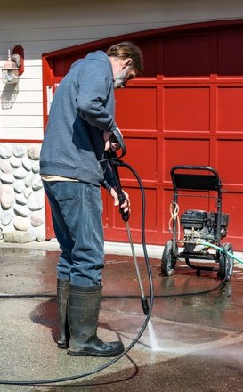 Tidal Wave Pressure Washing employee power washing driveway